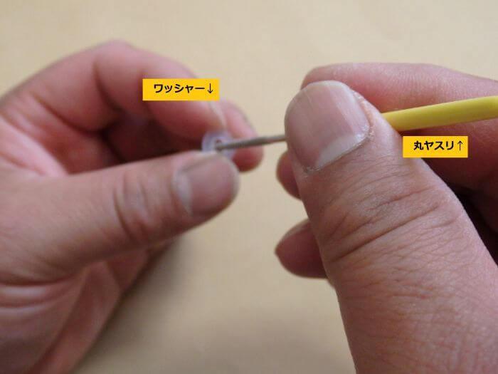 ワッシャーの内側を丸ヤスリで削って穴を大きくしている写真
