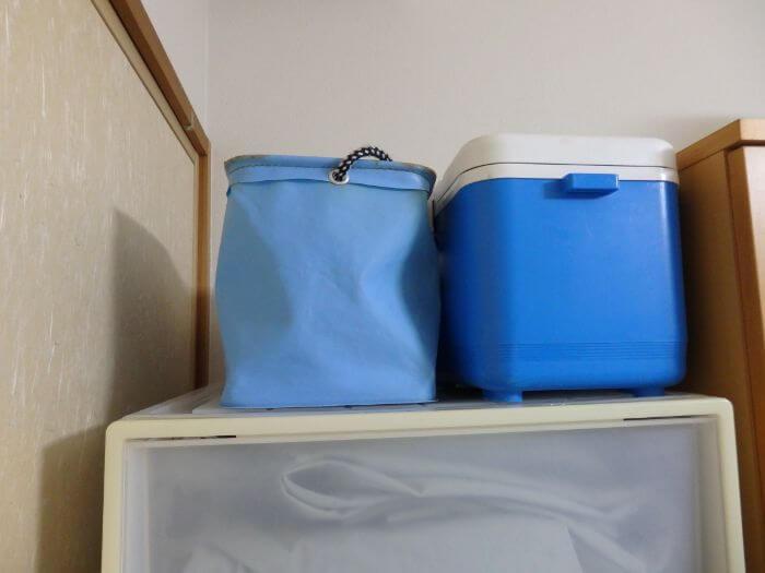 衣装ケースの上にクーラーや水汲みバケツを置いている写真