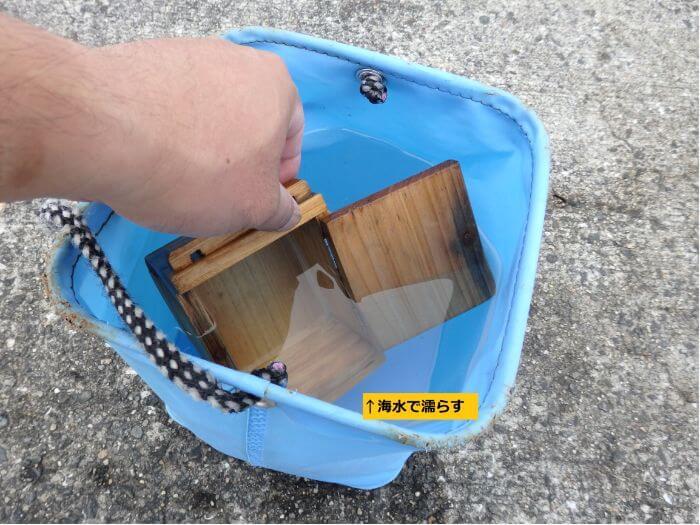 木製のエサ箱を海水で濡らしている写真
