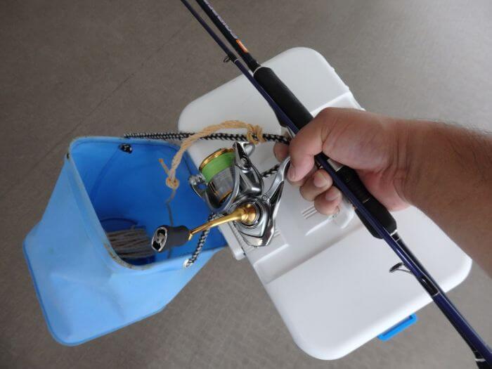 片手でクーラーと竿と水汲みバケツを持っている写真