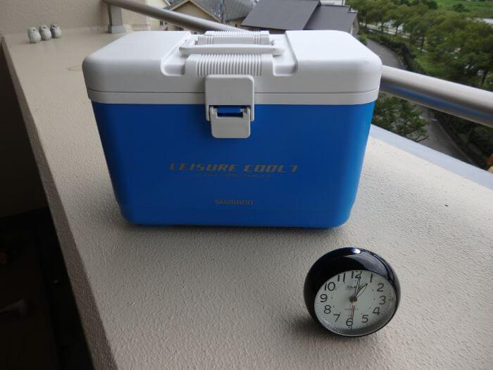 氷を入れたクーラーボックスをベランダの日の当たるところに置いている写真