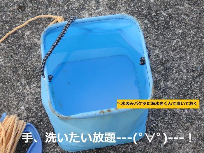 水汲みバケツに海水をくんで、手を洗えるようにしている写真
