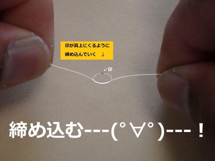 印が真上にくるように幹糸を締め込んでいる写真