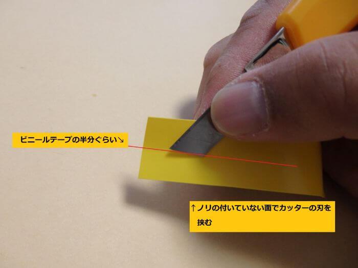 ビニールテープの半分のところにカッターを当てている写真