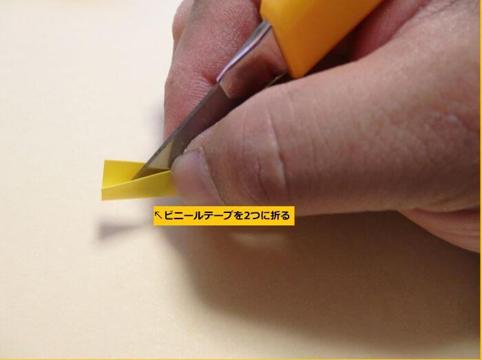 カッターの刃を軸にしてビニールテープを半分に折った写真