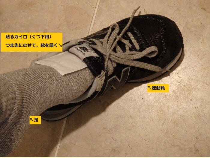 防寒対策のため、靴下の上にくつ下用カイロを乗せて靴を履く写真
