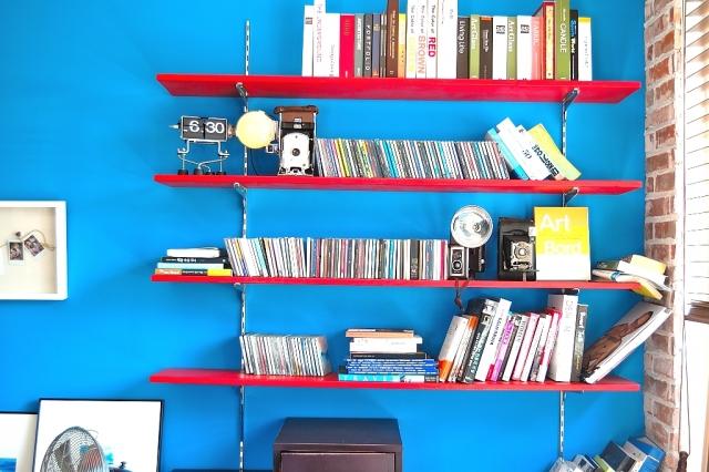 青い壁に取り付けられた赤い本棚