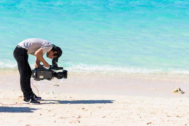 浜辺でビデオ撮影をする男性の写真