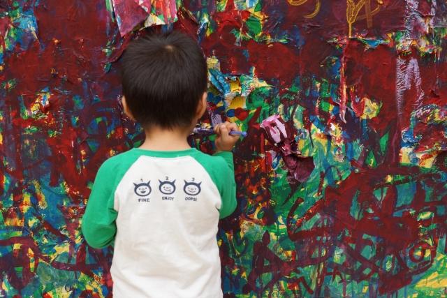 壁に落書きをしている子供の写真