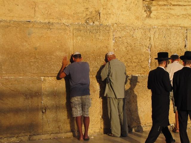 イスラエルにある、嘆きの壁の前に立つユダヤ教徒の写真