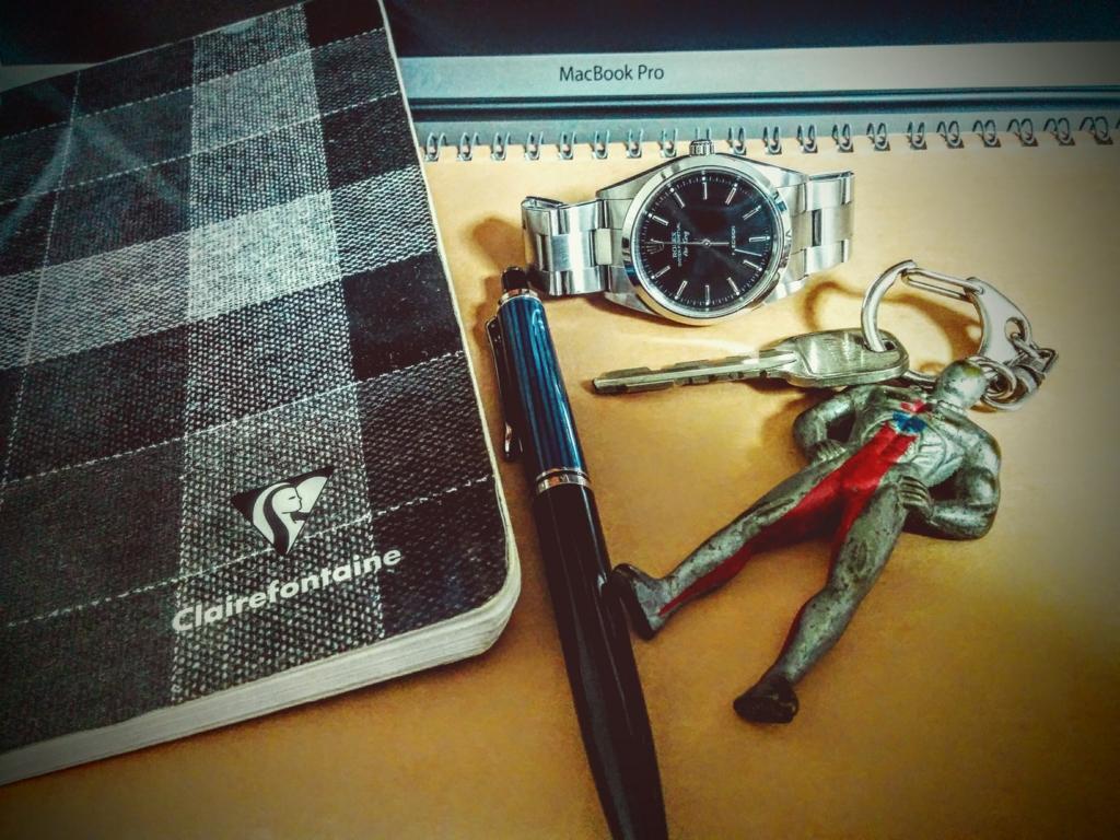 パソコンと腕時計とノートの写真