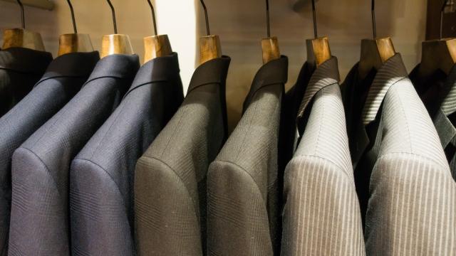 クローゼットにかけられた数着のスーツの画像