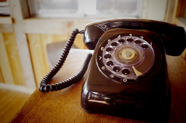 ダイヤル式の黒い電話の画像
