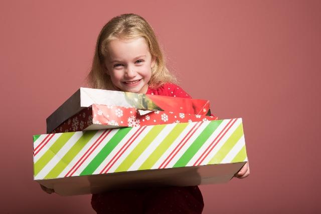 プレゼントの箱を手にして喜んでいる少女の写真