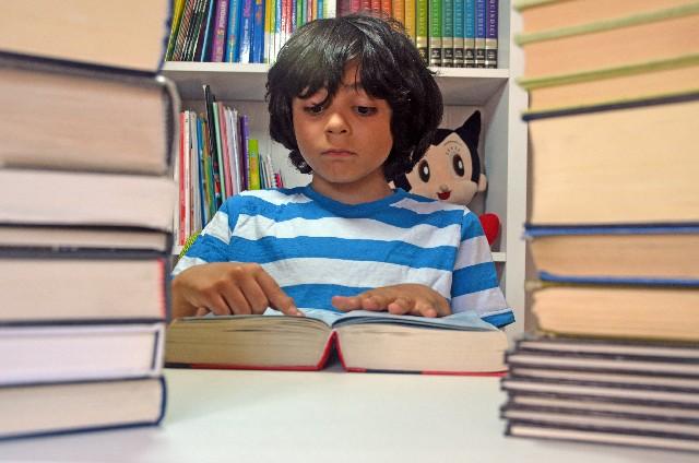 山積みした本の間で読書をする少年の写真