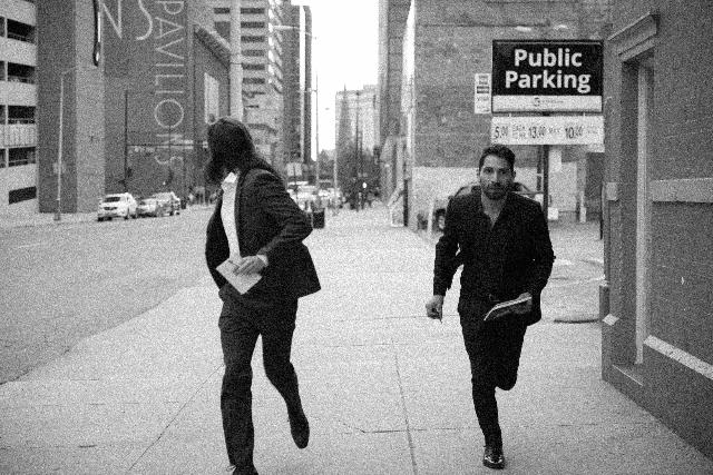 走りながら逃げる男性二人のモノクロ写真