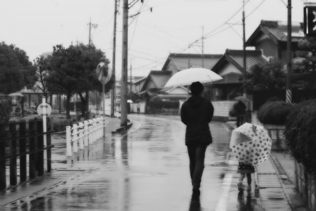 傘をさして歩く親子連れの写真
