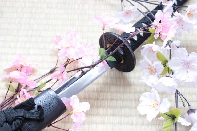 日本刀と桜の枝が並んでいる写真