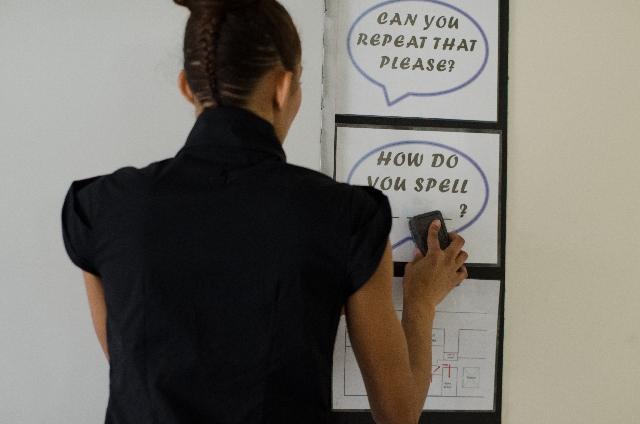 ホワイトボードに何か書いている女性の写真