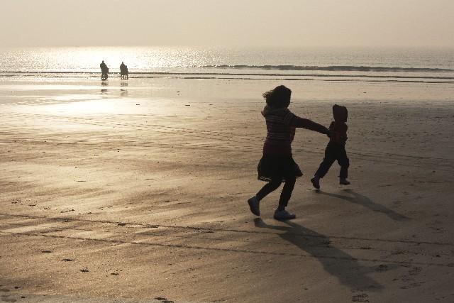 砂浜で遊ぶ子供達の写真
