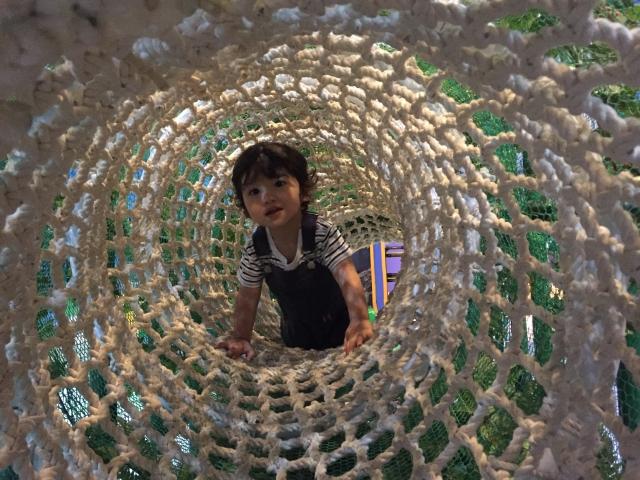 トンネルの遊具で遊ぶ女の子の写真