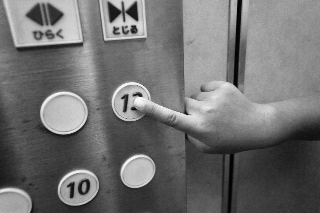 エレベーターのボタンを押そうとしている写真