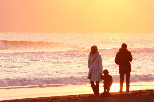 親子で黄昏時の浜辺を散歩している写真