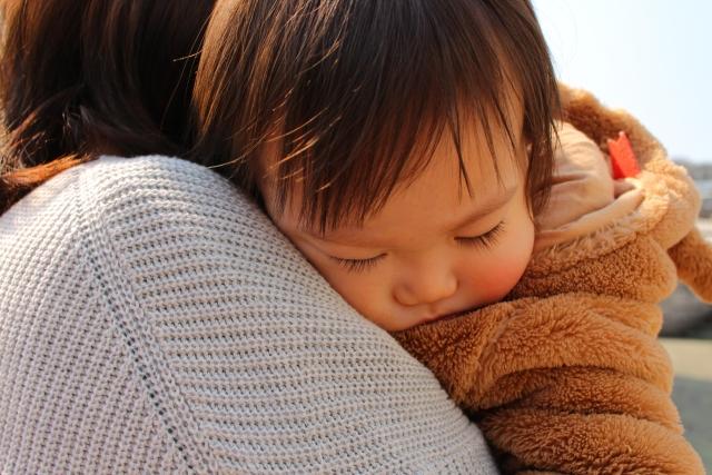 母親に抱かれて眠る子供の写真