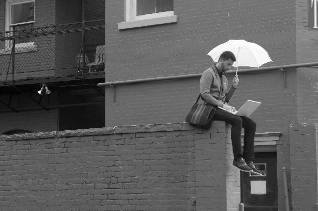 傘をさしてパソコンを操作している男性の写真