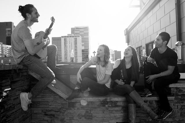 ギターを弾きながら歌っている人と仲間の写真