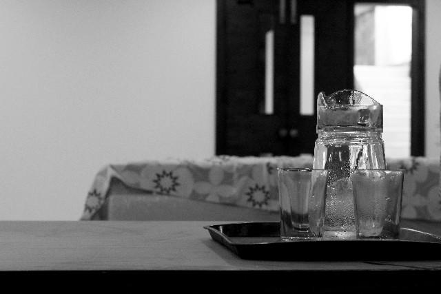 テーブルに置かれた水さしとコップのモノクロ写真