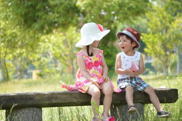 ベンチに座っておしゃべりをする男の子と女の子の写真
