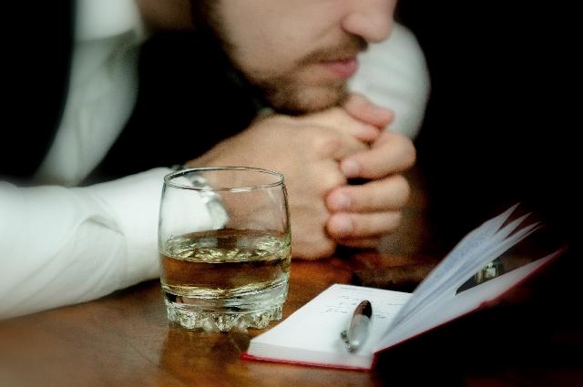 テーブルに顎を付けて冴えない感じの男性の写真