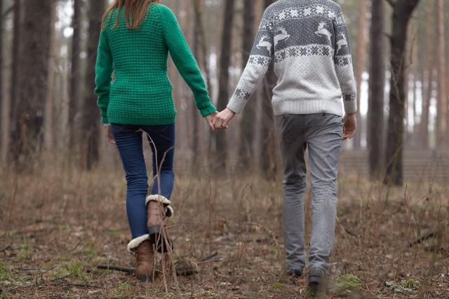 手をつなぐカップルの写真