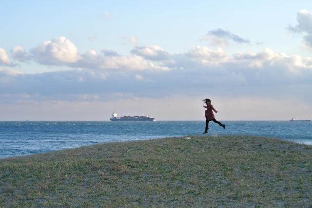 海辺でジャンプしている女性の写真