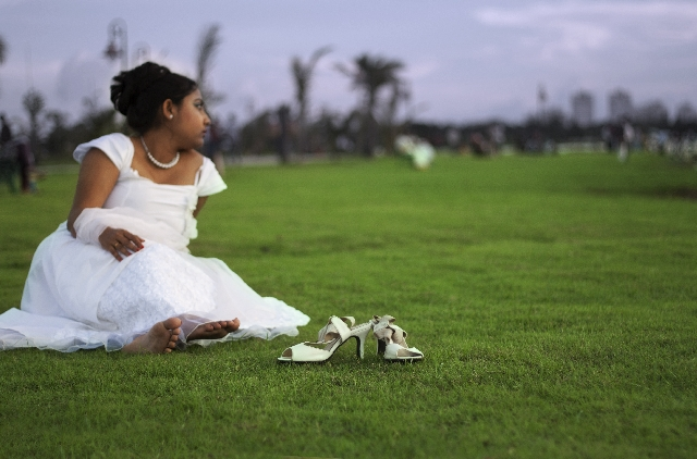 一人ぼっちで芝生に座るインド人花嫁の写真