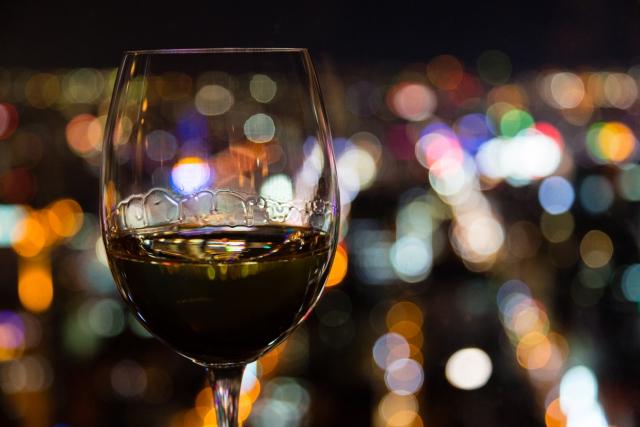 夜景に溶け込むワイングラスの写真