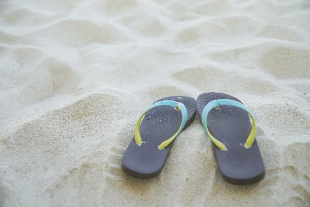 砂浜に置かれたビーチサンダルの写真