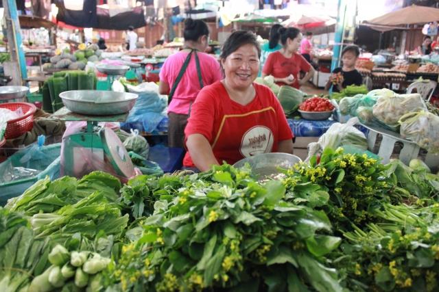 東南アジアの市場で野菜を売る女性の写真