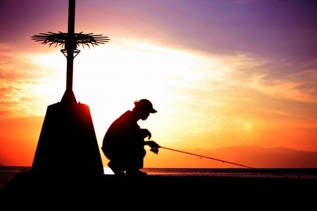 夕日の下で釣りをしている人の写真