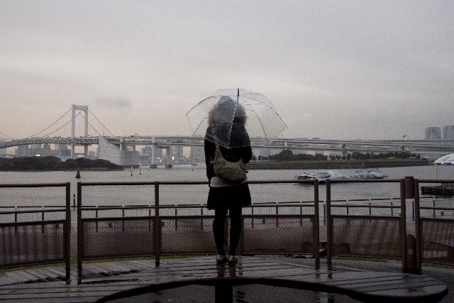 傘をさしている女性の後ろ姿の写真