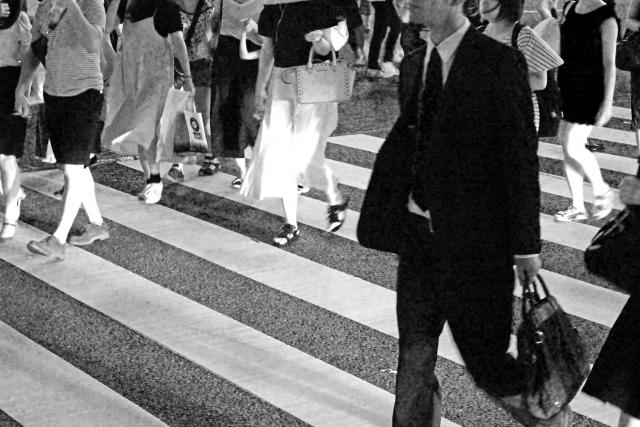 横断歩道を歩く人のモノクロ写真