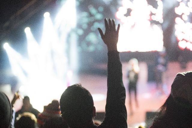 ステージに向かって手を挙げる男性の写真