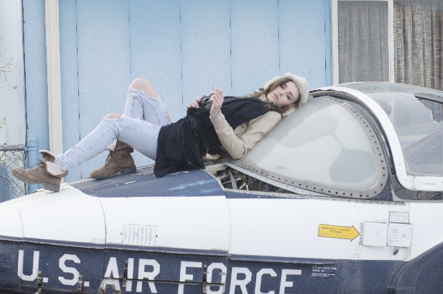 古びた戦闘機の上に寝そべる女性の写真