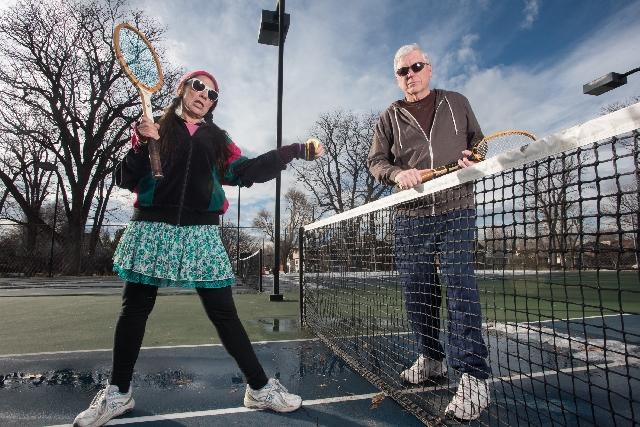 テニスをしている中年の男女の写真