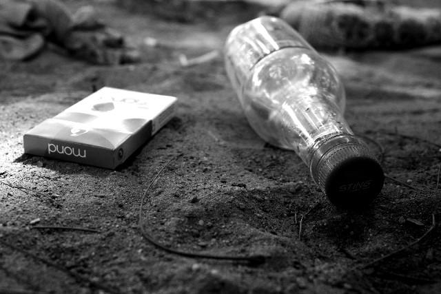 ポイ捨てされたペットボトルとタバコの箱の写真