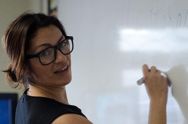 ホワイトボードに何かを書いている女性の写真