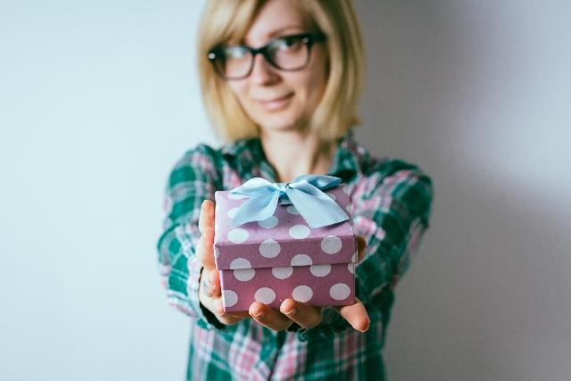 プレゼントを差し出す女性の写真