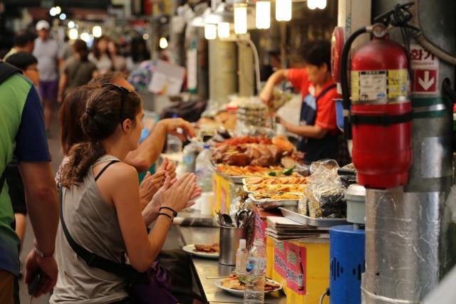屋台で料理を楽しんでいる観光客の写真
