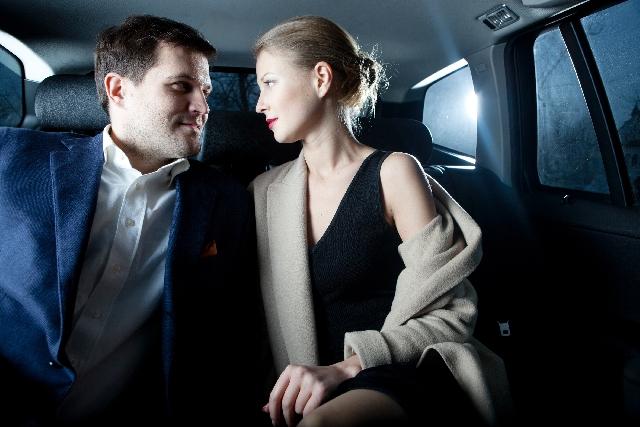 車の後部座席で見つめあう男女の写真